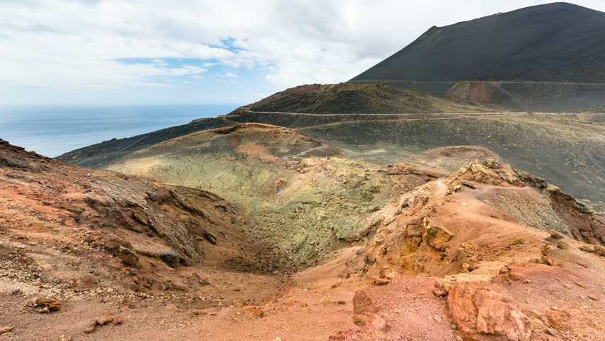 Timelapse sequence of the colorful crater of the volcano Teneguia in the south of La Palma with clouds passing by in 4K resoultion, zooming in. | Shutterstock HD Video #33102505