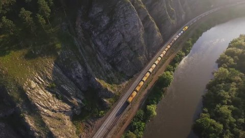 Freight train carries with oil tank an electric locomotive by two-sided Trans Siberian railway along the river in the Ural Mountains - Aerial Photography, top view