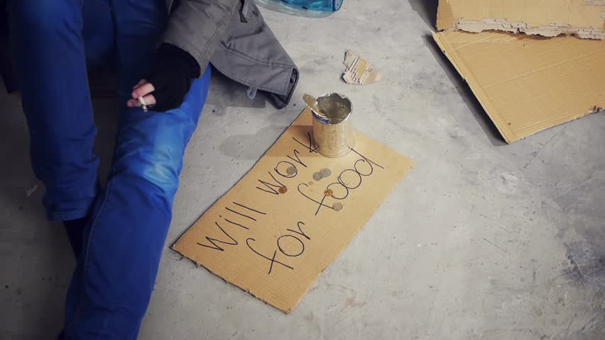 homeless man sitting on the floor and smoking cigarette