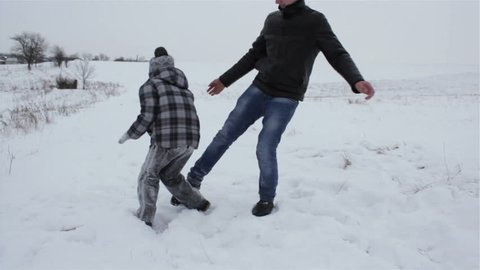 playing the snowballs of the guys,boy playing with older brother in snowballs