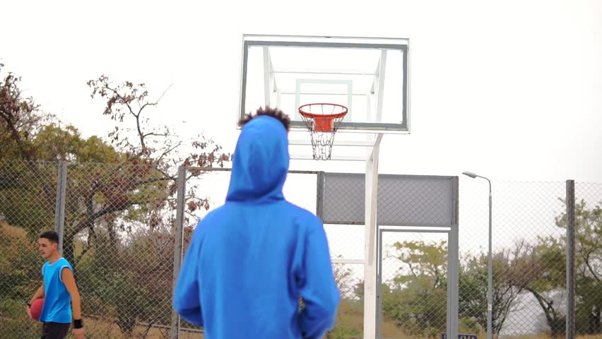 Young african american playing basketball on the street and throwing a ball to the basket unsuccessfully. Slowmotion shot