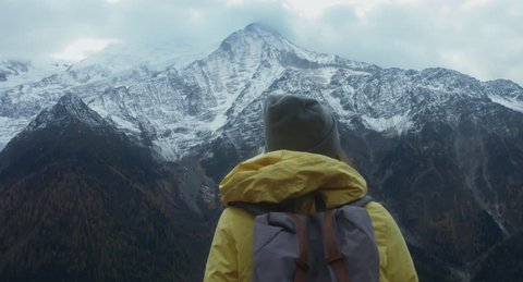 CRANE SHOT Beautiful Caucasian female hipster hiking in French Alps, enjoying the view of Mont Blanc massif. 4K UHD RAW 60 FPS SLO MO