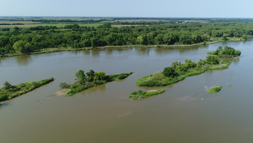 Aerial drone view of the Platte River and pasture in Nebraska. Footage shows a wide shallow sandy ri...
