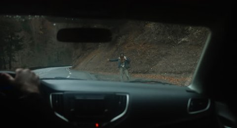 POV Car driver stops to pick hitchhiking girl on a forest road in mountains. 4K UHD 60 FPS SLO MO