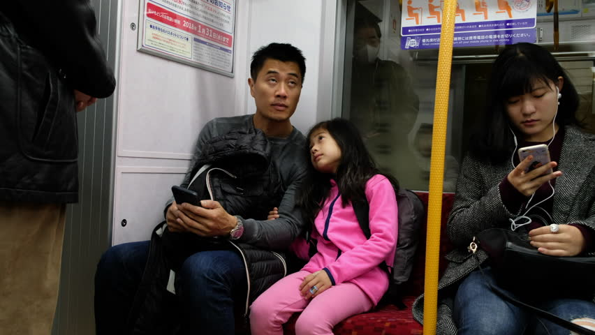 TOKYO, JAPAN - NOVEMBER 17TH, 2017. Father and daughter with smartphone in a Tokyo Metro subway train.  | Shutterstock HD Video #33185995