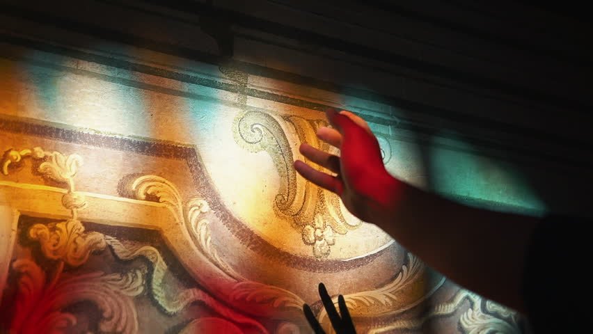 Man's hand in the colorful sunrays before a wall with paintings