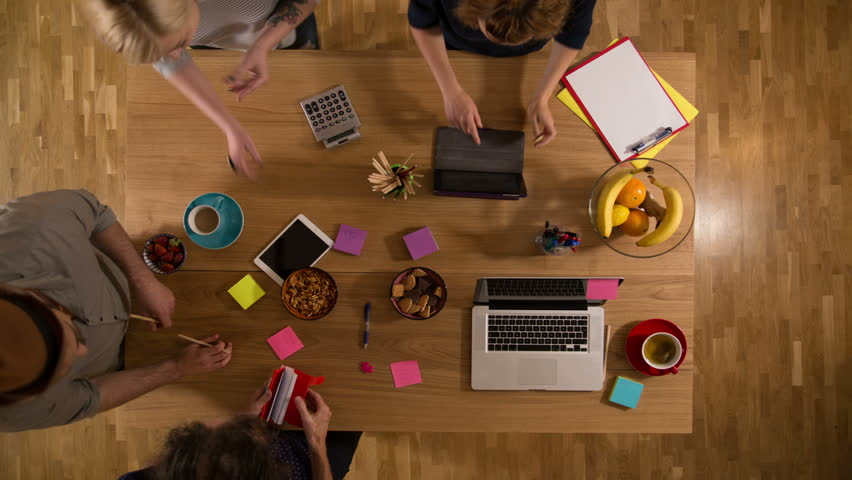 Timelapse view from above of a desk with two women and two men working together  | Shutterstock HD Video #33202582