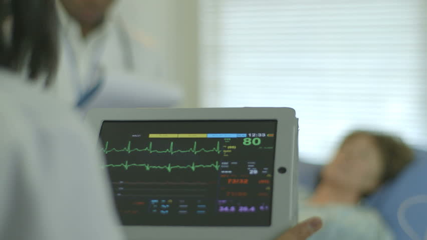 A doctor or nurse in a hospital setting looks at the vitals and other data being displayed on a portable patient monitor she is holding.