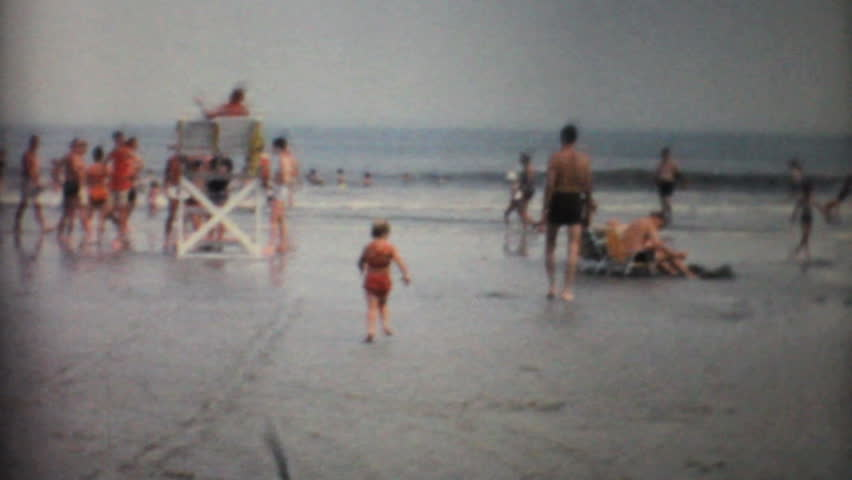 ST. AUGUSTINE, FLORIDA - JUNE 3, 1967 - 8mm film footage of a cute little girl enjoys spending time splashing in the waves on a Florida beach in 1967.