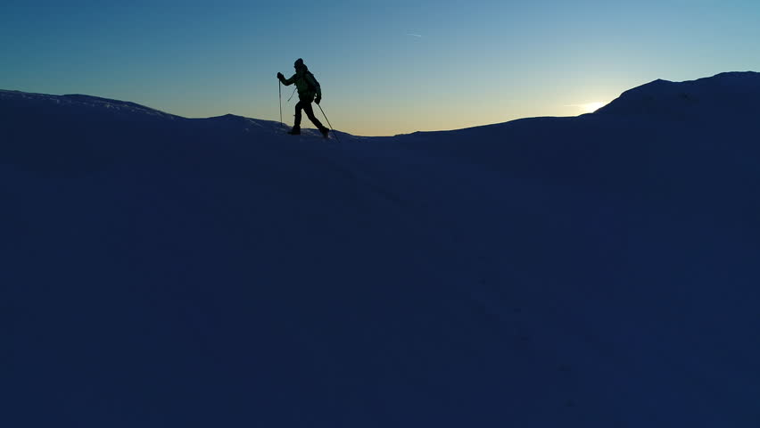 Aerial, slow motion - Extreme recreational pursuit of adult male in winter clothing running on snowy mountain top with trekking poles and a backpack at sunset. Silhouette of a man running on mountain  | Shutterstock HD Video #33212647