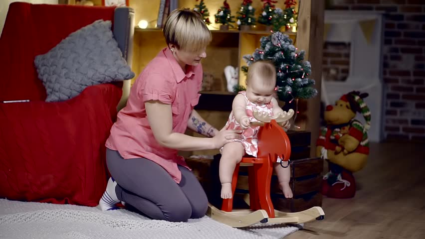 mother playing with baby girl in the rocking horse. children's room with a festive interior