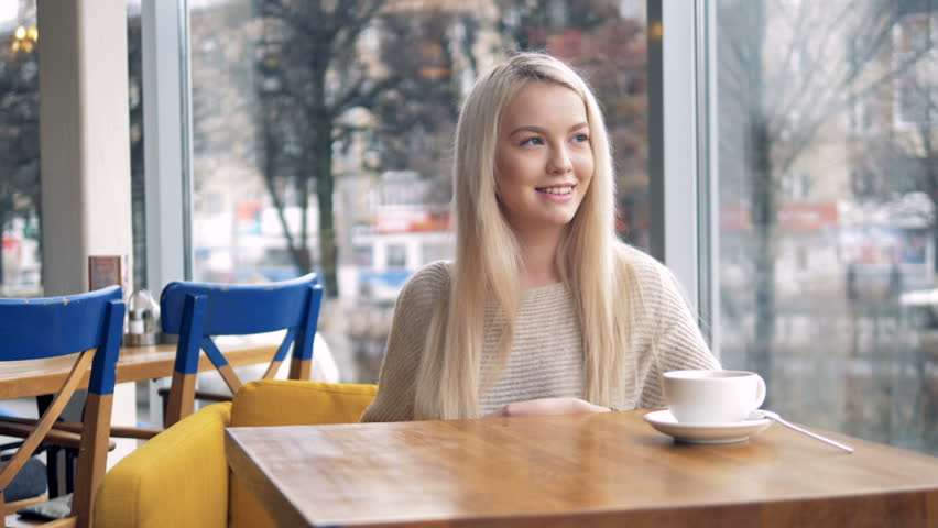 A smiling young woman makes a contactless payment at a cafe table.