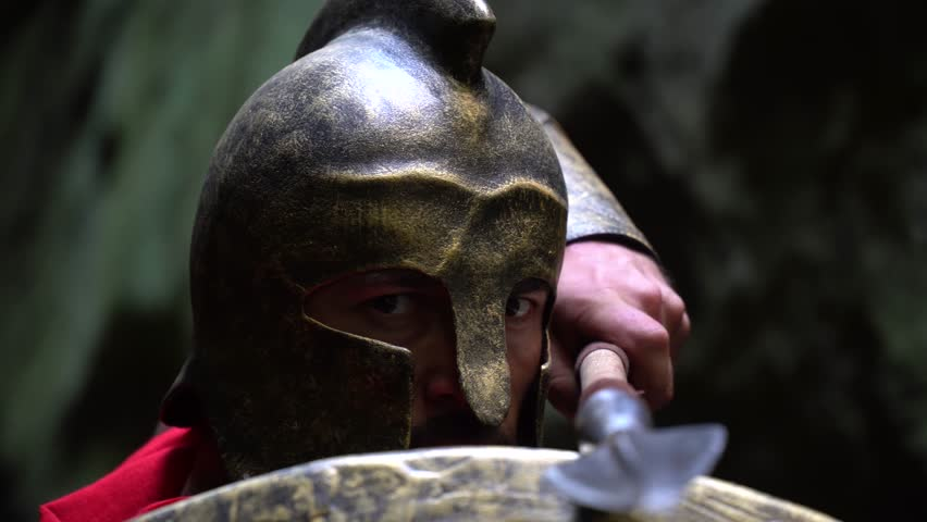 Closeup of a mature spartan soldier wearing a helmet hiding behind his shield looking to the camera fiercely holding a spear ready to fight bravery confidence masculinity concept.