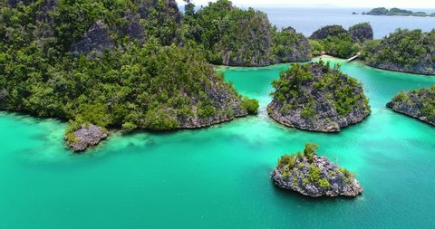 AERIAL: Pianemo Islands, Blue Lagoon with Green Rocks, Raja Ampat, West Papua, Indonesia.