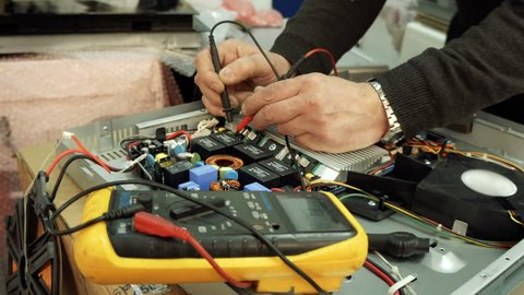Service center. Electronics repair shops. A man repairs the hob. Multimeter.