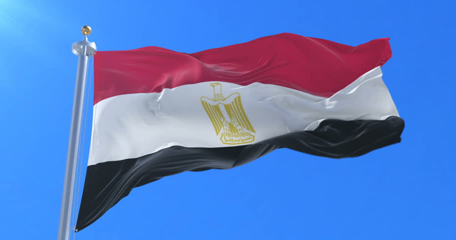 Flag of Egypt waving at wind with blue sky in slow, loop