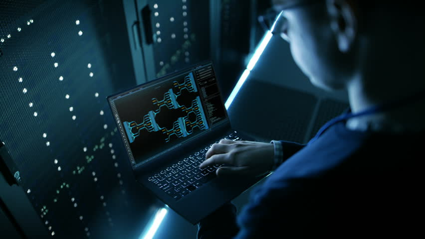 Data Center Engineer Holds Laptop and Works Controls System Stability. Shot on RED EPIC-W 8K Helium Cinema Camera.