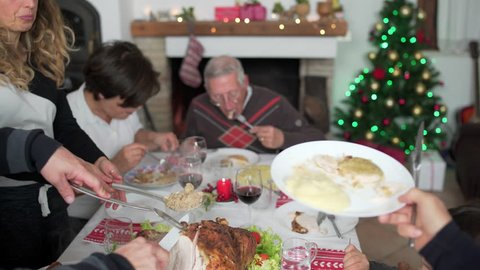 Happy large family eating together and serving roasted turkey during Christmas dinner at xmas time and winter holidays.