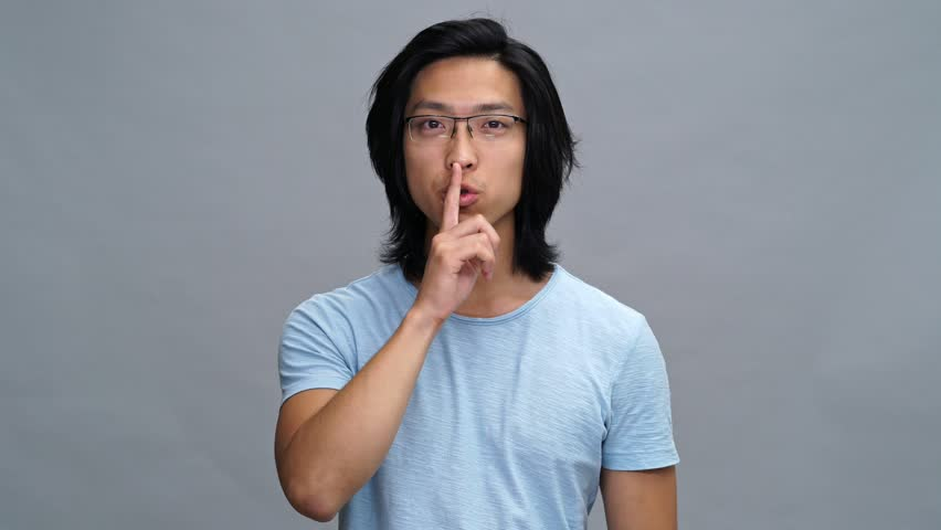 Handsome smiling young asian man showing silence gesture | Shutterstock HD Video #33255025