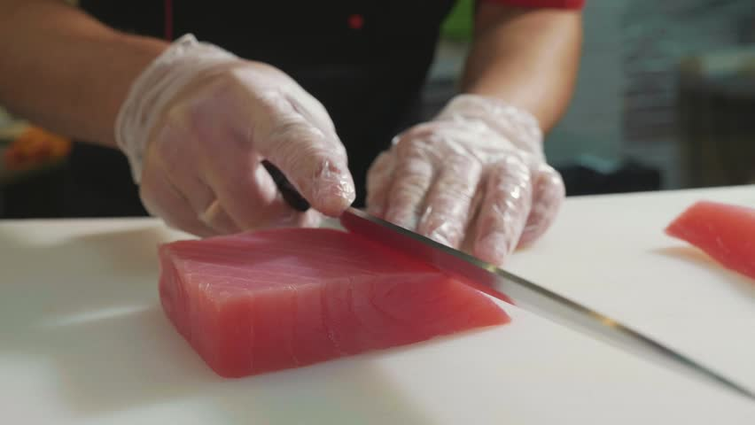 Close-up of sushi chef in gloves slices fresh fish at sushi bar. Professional cook cutting fish fillet at commercial kitchen, slow motion.