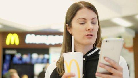 MOSCOW, RUSSIA - CIRCA November 2017: Teen girl drinking soda from paper cup at McDonald's fast food restaurant on food court. Woman using cellphone, browsing, reading news, chatting with friends