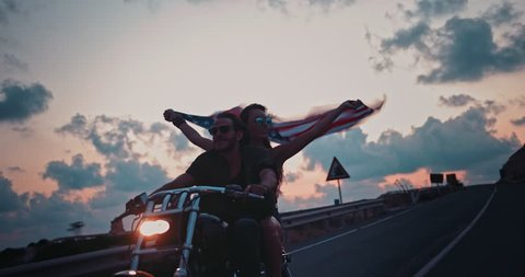 Young woman riding motorcyle with macho boyfriend holding American flag and celebrating fourth of July