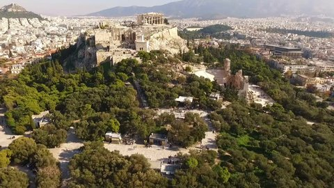 Aerial birds eye view video taken by drone of iconic Acropolis hill and the Parthenon, Athens historic center, Attica, Greece