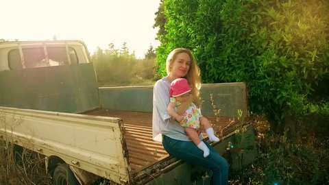 Happy mother holding daughter in arms and sitting in back farm pickup truck. Smiling mom with daughter on hands looking at camera on pickup truck background. Young mom and daughter on rural farm
