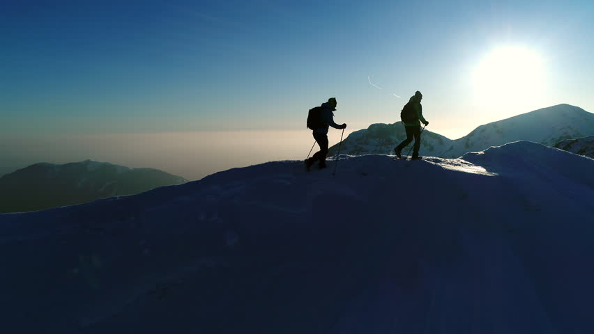 Aerial - Flyover hikers equipped with warm clothes, backpacks and trekking poles exploring the winter wonderland in Julian Alps. Two adult male mountaineers walking on snowy mountain top at sunset  | Shutterstock HD Video #33334747