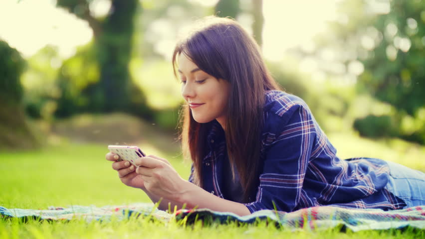 Happy female blogger using smartphone at park