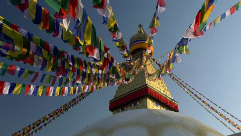 Prayer flags at Boudhanath Stupa in sunrise lights. Kathmandu, Nepal . Crane shot, UHD, 4K