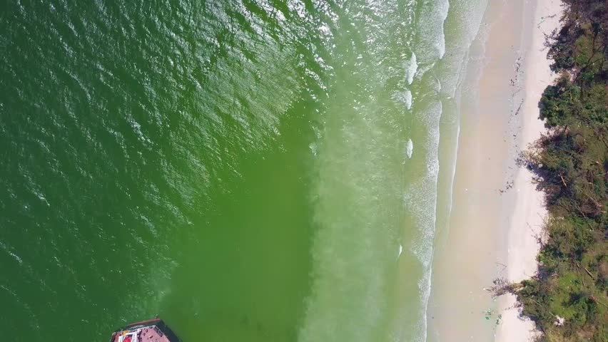 vertical aerial view pictorial azure sea washes huge tanker vessel grounded on island beach under scorching sun