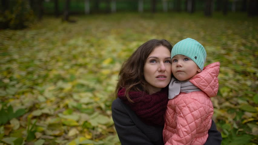 Mom with a baby in autumn park. Happy young mother and baby girl resting in the autumn forest. slow-motion | Shutterstock HD Video #33368395
