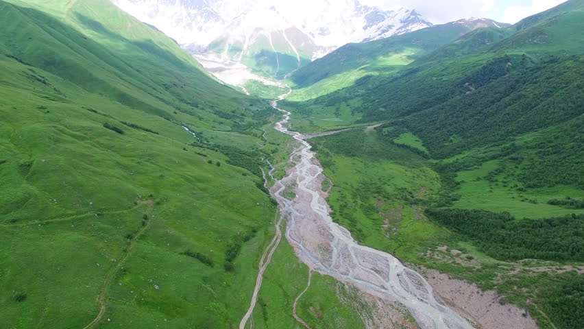Flying over rocky mountain river in green valley 4k Aerial view nature video landscape background panorama. Water flows, snow peak green ridge hills on blue sky and clouds in Caucasus, Georgia