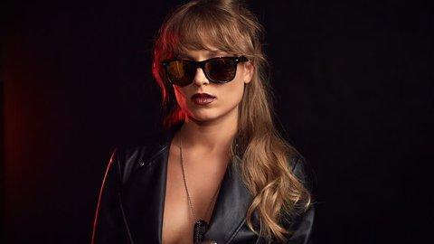 Portrait of elegant blonde woman in glasses smoking a cigarette on black background in studio