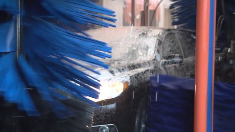 Black car being soaped and washed by large brushes inside a car wash
