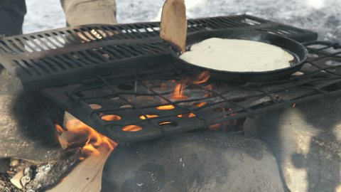 Process of cooking traditional russian pancakes on frying pan on bonfire during Shrovetide carnival