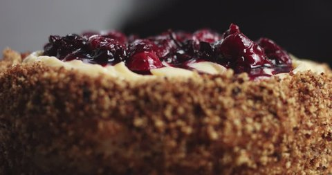 Adding forest berries compote to the top of a custard cream sponge cake, close up video