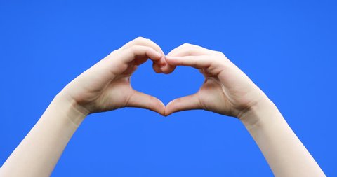 Asian young woman making love heart gesture with hands on blue background