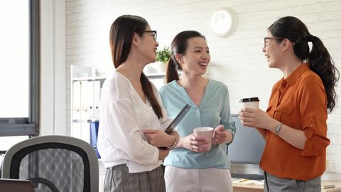 three businesswomen enjoy the girls talk in the office and drinking coffee together at afternoon tea break time.