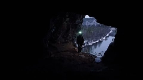 Man Silhouette Exploring a Cave. Scientists  exploring dark caves. Speleology man descent into the cave.