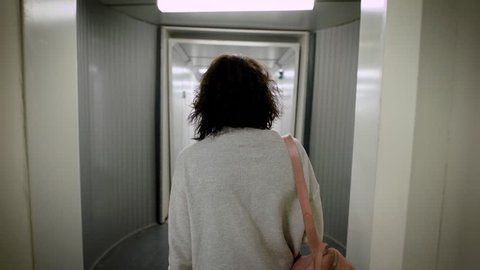 sad tired young brunette is dressed in casual style, is walking inside a light modern jet bridge, back view