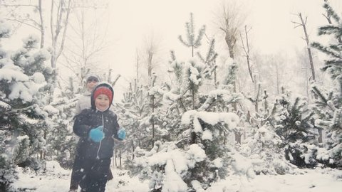 Kids are having fun running between snow trees in winter time, happiness concept