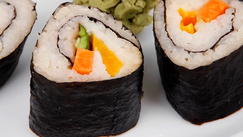 Japanese Traditional Cuisine - California Roll with Salmon (sake) Cream Cheese and Tuna (maguro) . on white dish with sticks isolated over white background