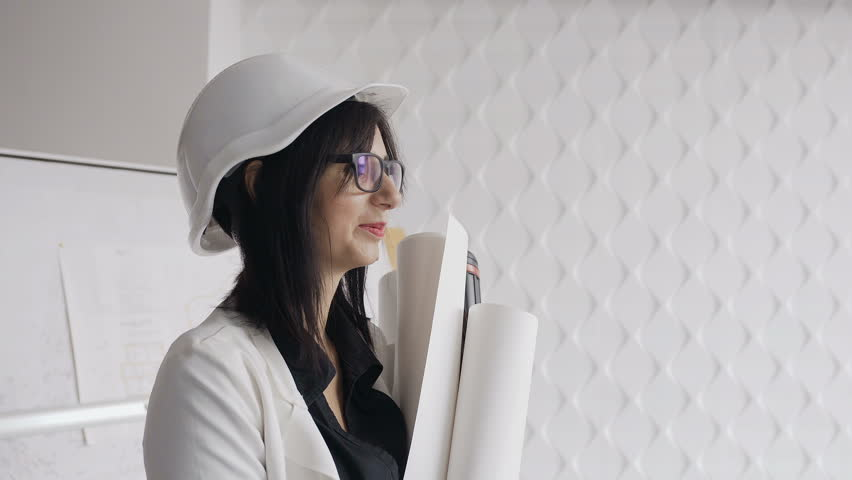 Close-up of a woman's architect in eyeglasses and a protective helmet that stands next to the table a drawing design construction of a private home and holds in the hands of mock-ups of other projects | Shutterstock HD Video #33499315
