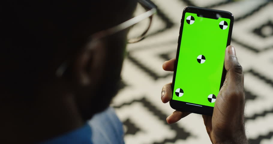 Over shoulder view on african american man holding a black smart phone vertically with green screen and tracking motion. Chroma key. Patterned background