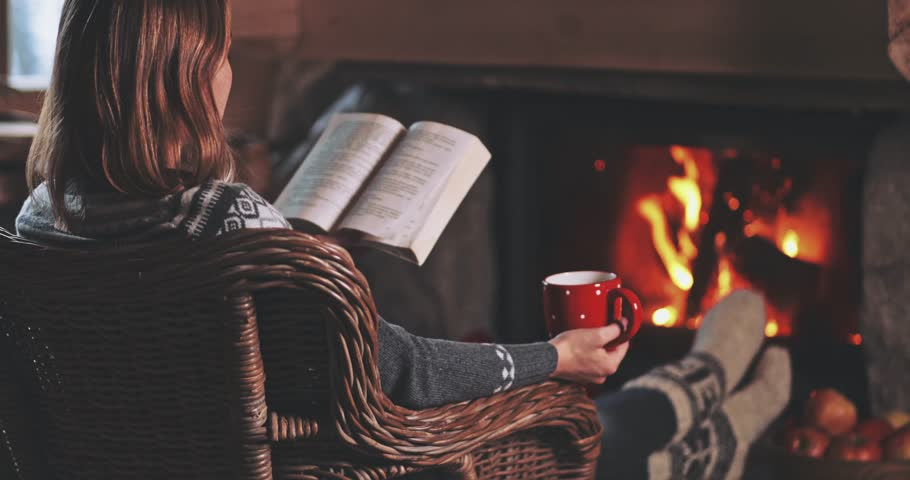 Woman Reading a Book by the Fireplace. SLOW MOTION 4K. Young woman reading a book by the warm fireplace decorated for Christmas. Relaxed holiday evening concept. #33513415