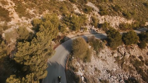 Drone follows adventure traveler riding his motorcycle on epic scenery serpentine mountain roads toward the town next to ocean. He descending from top to down after his trip