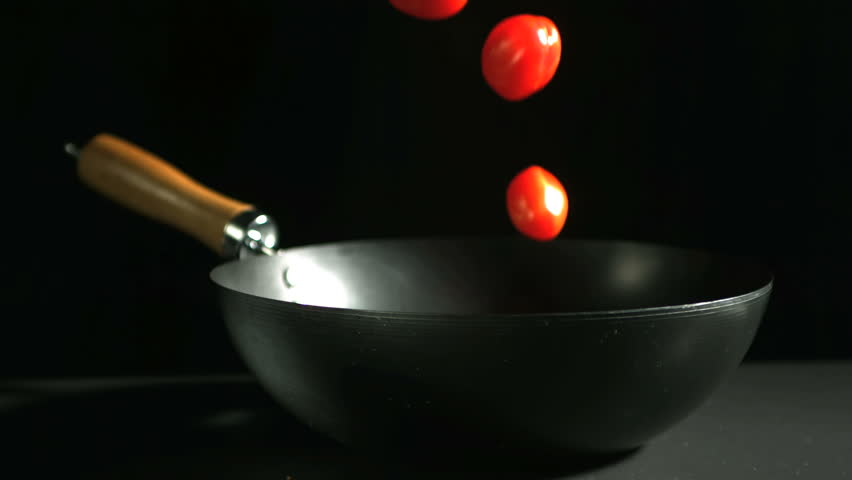 Cherry tomatoes falling into wok in slow motion