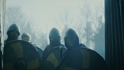 Large-Scale Medieval Battle Reenactment. Violent Tribe of Warriors Run Through The Gates of the Wooden Fortress and Attack Guards.  Shot on RED EPIC-W 8K Helium Cinema Camera.